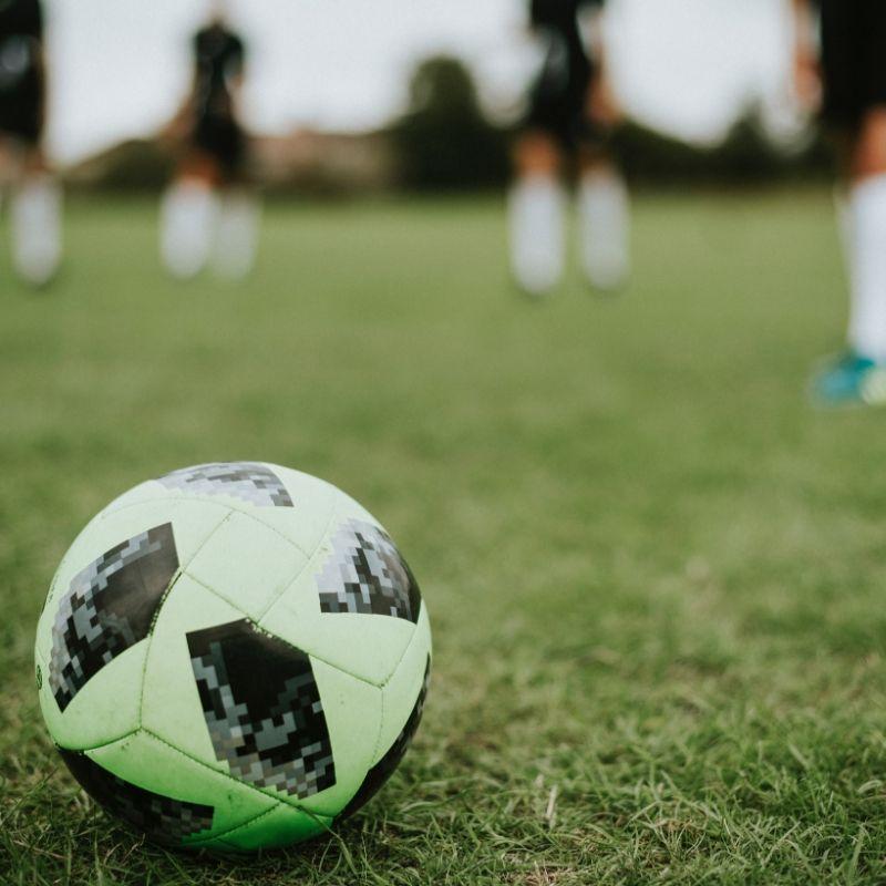Piłka nożna leżąca na trawie wśód zawodników na obozie piłkarskim