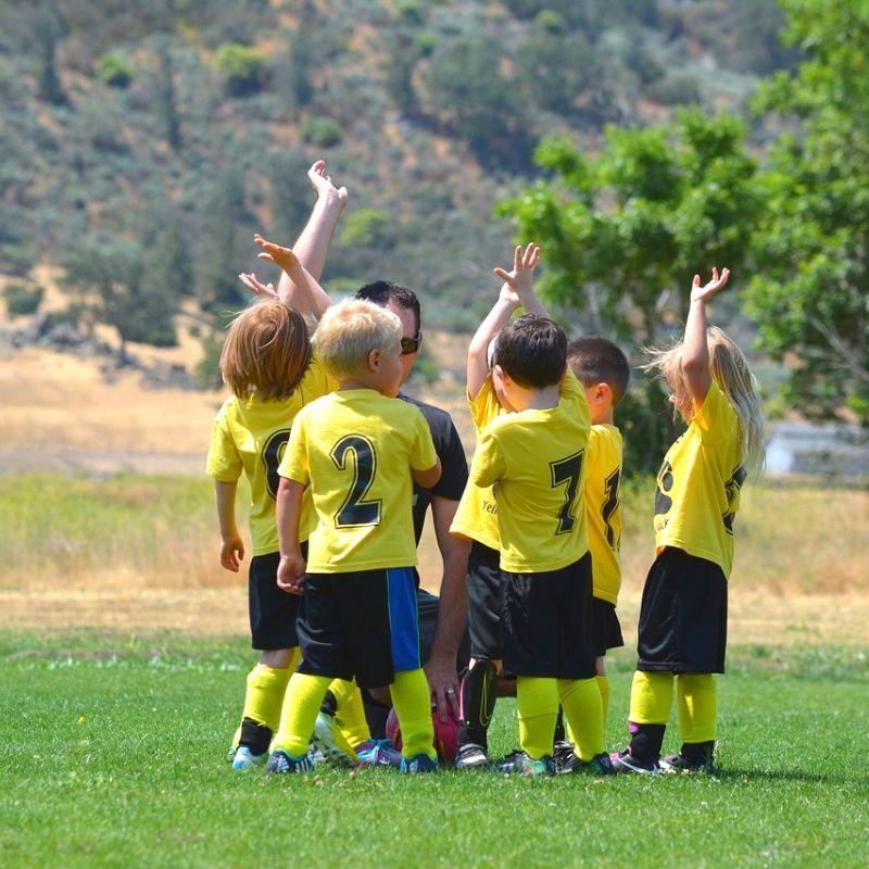 Dzieci w strojach piłkarskich stojące na zbiórce przy trenerze piłkarskim