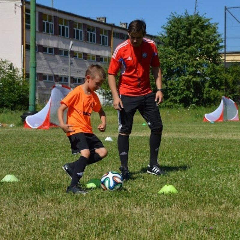 Trener piłki nożnej na treningu indywidualnym z młodym zawodnikiem