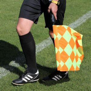 Sędzia piłkarski trzymający flagę spalony w piłkce nożnej