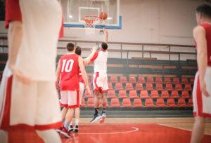 drużyna koszykarska grająca na boisku do koszykówki w strojach koszykarskich